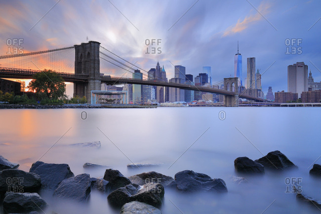 New York City, USA - July 31, 2016: View from Dumbo towards Lower Manhattan and Financial District skyline across the East River with Brooklyn Bridge and Freedom Tower in the background