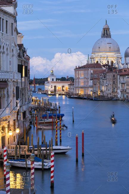Veneto, Italy - September 7, 2016: Grand Canal, Gondola rowing in Grand Canal at dusk, on the background Punta della Dogana and Santa Maria della Salute church