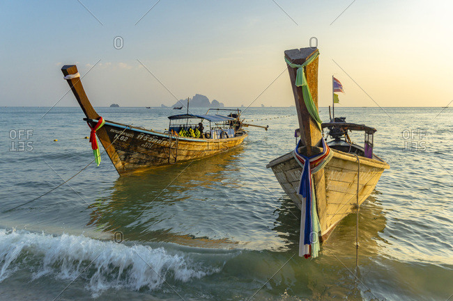 Krabi, Thailand - March 7, 2016: Typical Thai boat on the seaside of Ao Nang beach at sunset