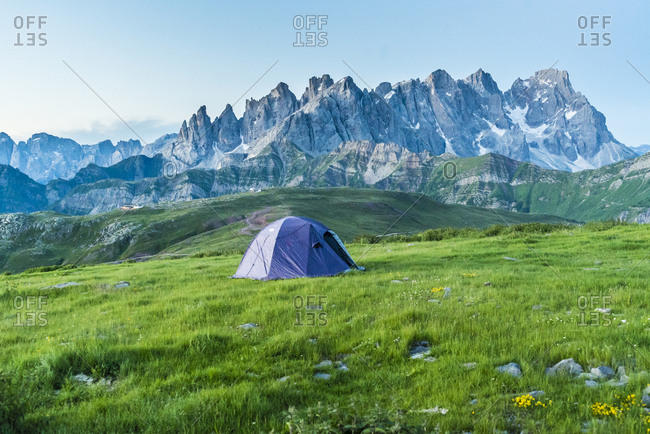 Passo Valles, Tent on the grass on Col Margherita Early morning with Pale di San Martino Dolomites in background