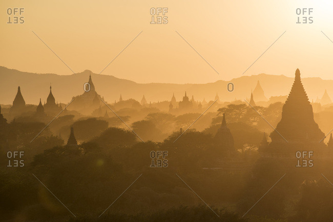 Stupas silhouettes in the fog at sunset