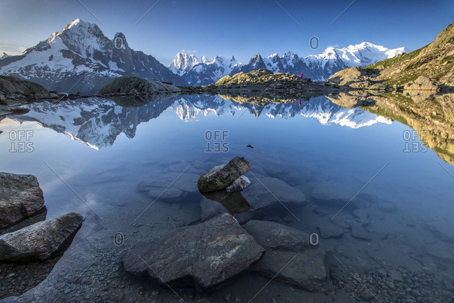 Snowy peaks of Aiguilles Verte Dent Du Geant and Mont Blanc are reflected in Lac Blanc