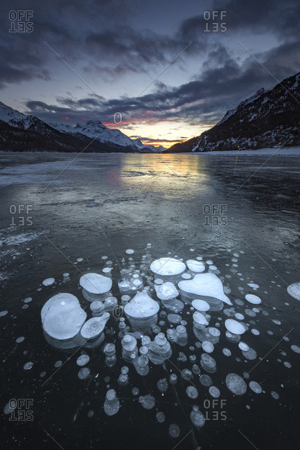 Frozen gas bubbles trapped in the ice after sunset, Silvaplana Lake