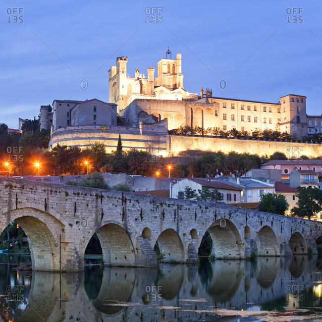 Cathedral of Saint-Nazaire and the old bridge (Pont Vieux) on the Orb River illuminated at dusk