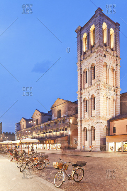 Ferrara, Italy - December 15, 2016: Piazza Trento e Trieste, bell tower of the Cathedral and Loggia dei Merciai illuminated at dusk