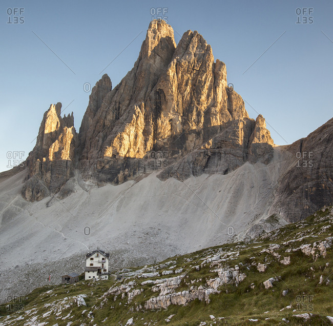 The alpine hut of Zsigmondy-Comici with the Croda dei Toni on background lit by sunset