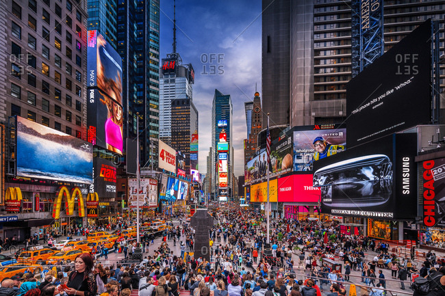New York City, USA - July 31, 2016: Visitors at Times Square Pedestrian Mall at night with taxi