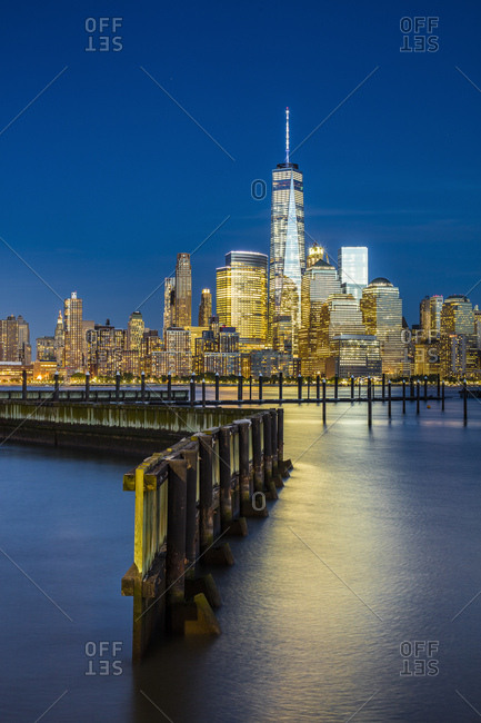 Lower Manhattan skyline with One World Trade Center and Freedom Tower from New Jersey, at night from new port