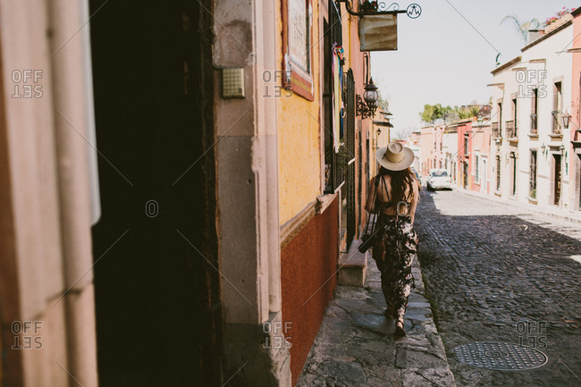 Woman walking down a cobblestone street in Mexico