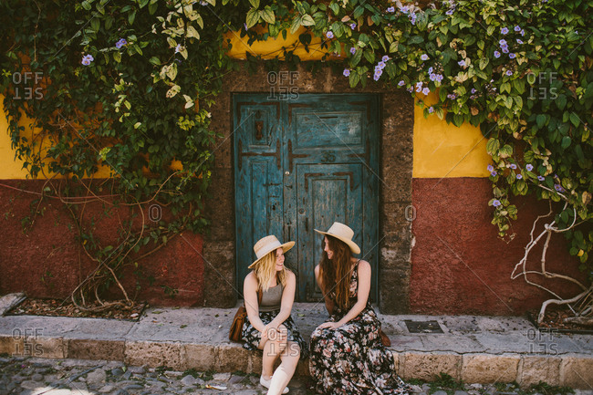 Two women sitting on sidewalk on vacation together