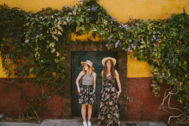 Two women in front of colorful door and wall