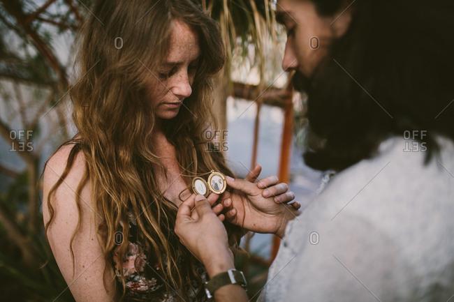 Man looking at a woman's locket