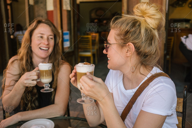 Two women drinking coffees together