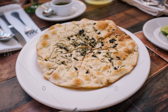 Pita bread topped with herbs on a plate