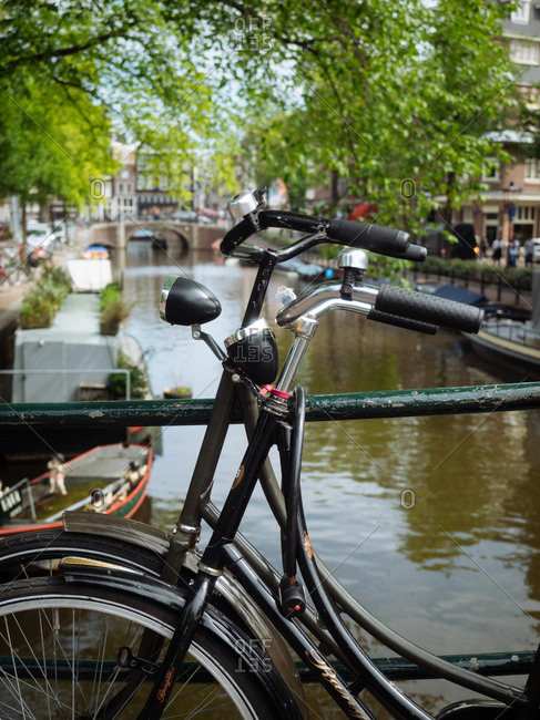 Amsterdam, Netherlands - July 20, 2015: Bikes chained to a canal railing