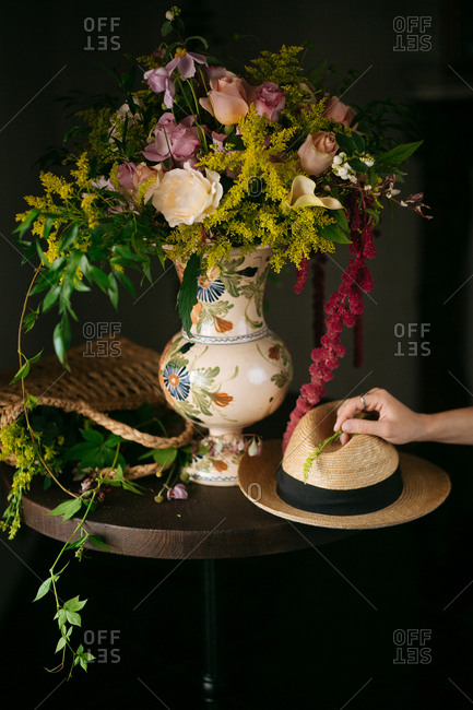 Person putting hat by flowers