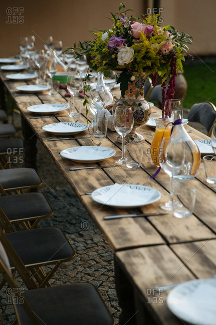 Wood tables prepared for dinner outdoors