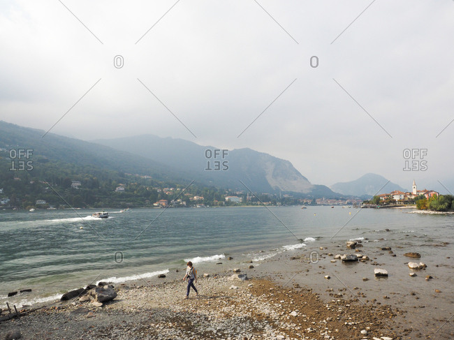 Stresa, Italy - March 3, 2017: Woman walking on the shore