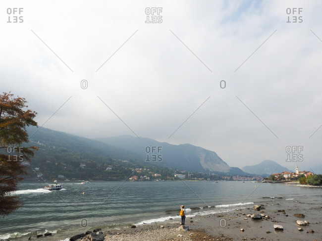 Stresa, Italy - March 3, 2017: Woman standing on the shore