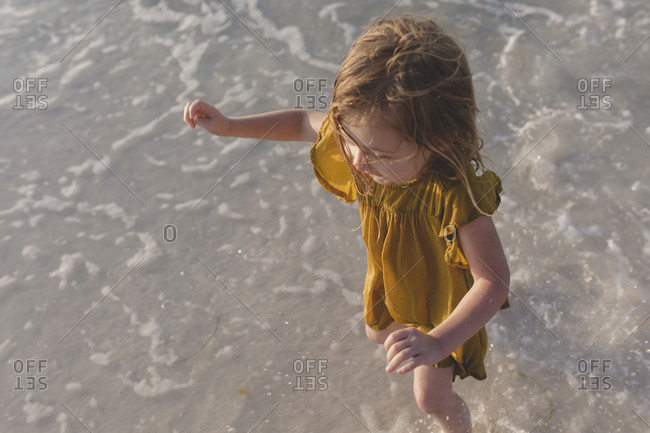 Young girl in yellow dress playing in the ocean surf