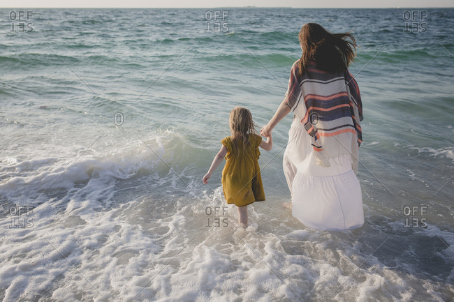 Mother and daughter holding hands as they walk into the ocean