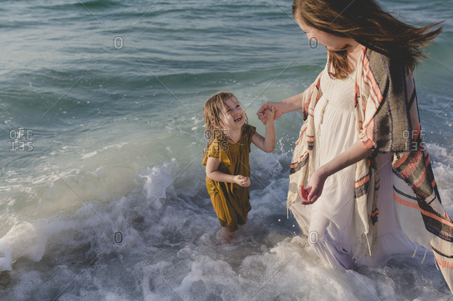 Little girl and her mother laughing as they play in the ocean surf