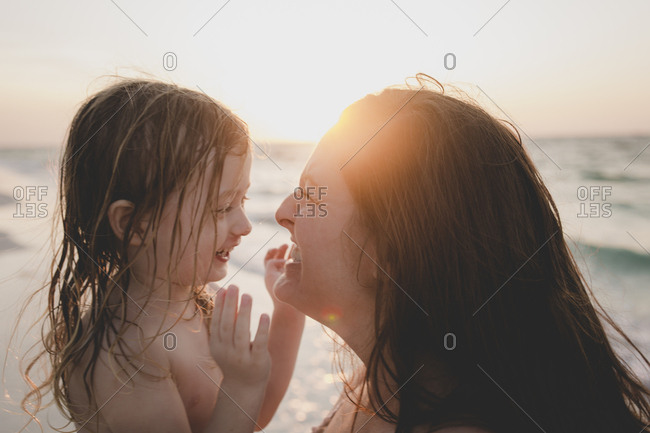 Little girl and her mother laughing and smiling at each other at the beach at sunset