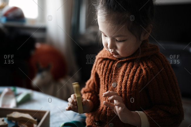Cute girl playing with wooden toys