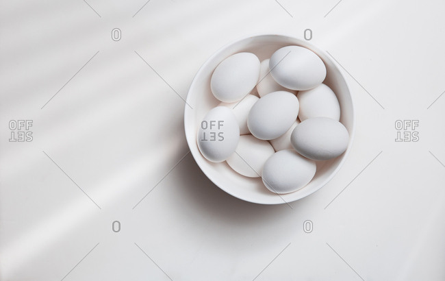 Hen eggs in a white bowl on a table