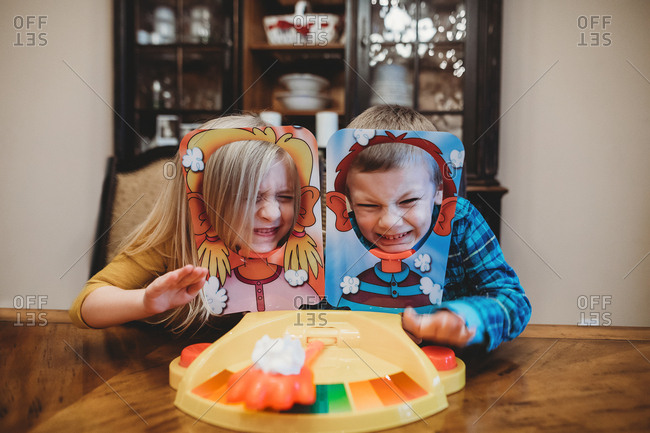 Two kids reluctantly play pie in face game