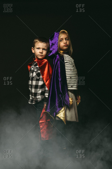 Two young siblings in superhero capes and fog
