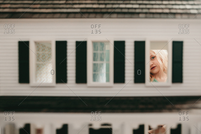 Young girl seen through the window of a dollhouse