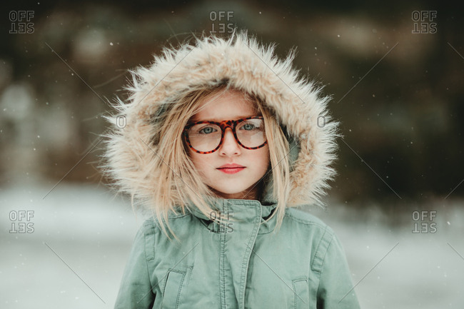 Beautiful young girl in hooded coat and glasses