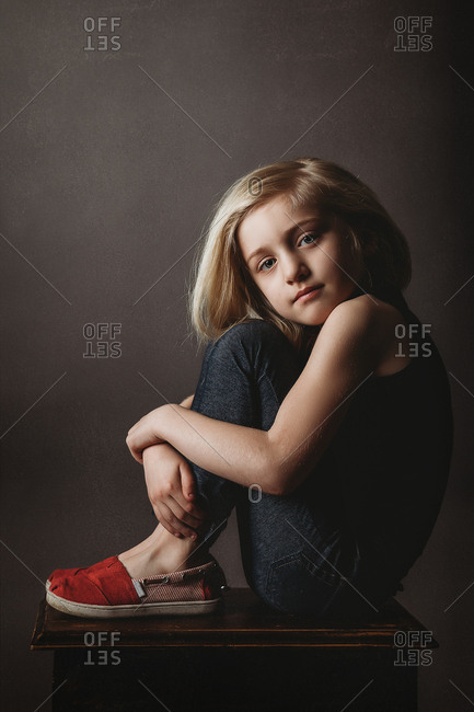 Portrait of a beautiful young girl sitting with knees up