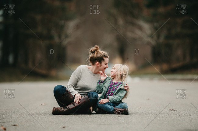 Affectionate mother and daughter sitting in street
