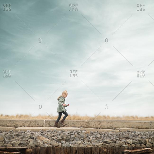 Young girl walking on rock wall