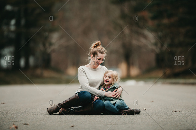 Portrait of mother and daughter sitting in street