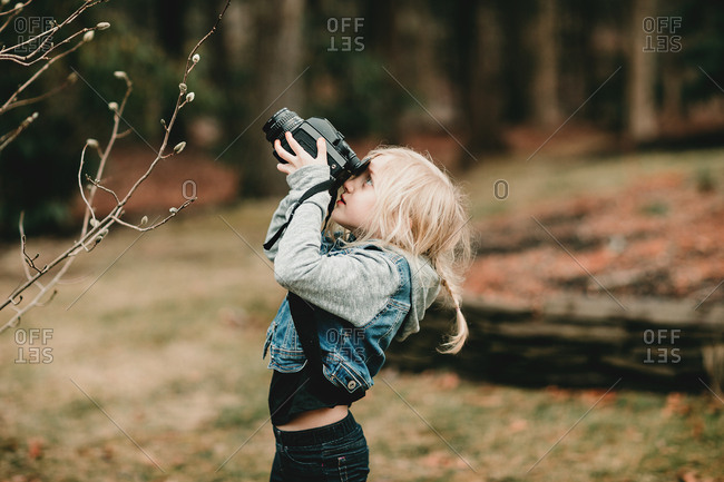 Young girl looking through camera at spring buds
