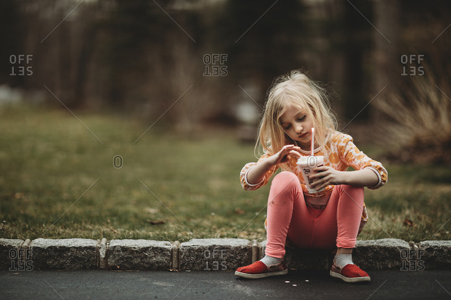 Girl sitting on curb with smoothie