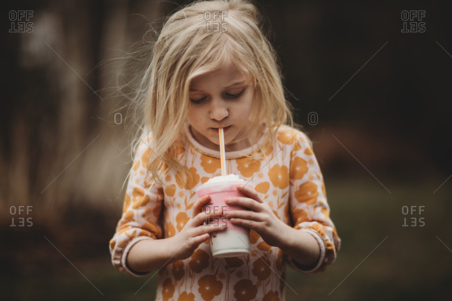 Young girl drinking a smoothie