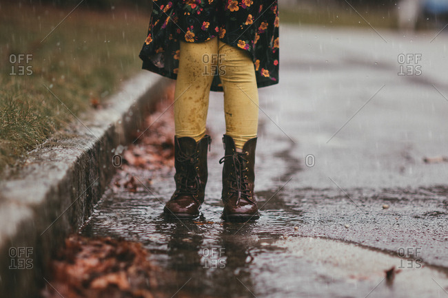 Girl in boots splashing in mud puddle