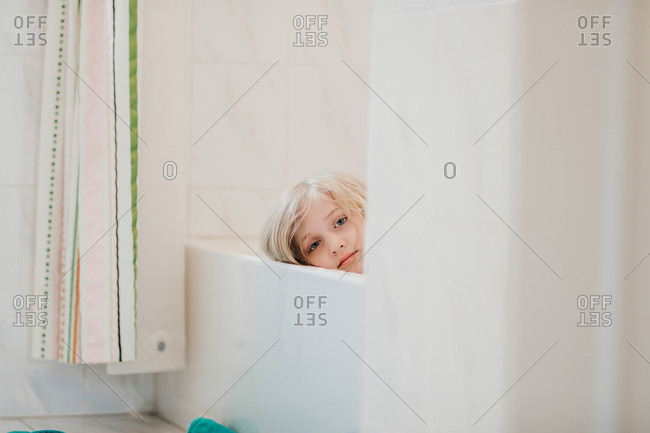 Portrait of young girl relaxing in bath tub