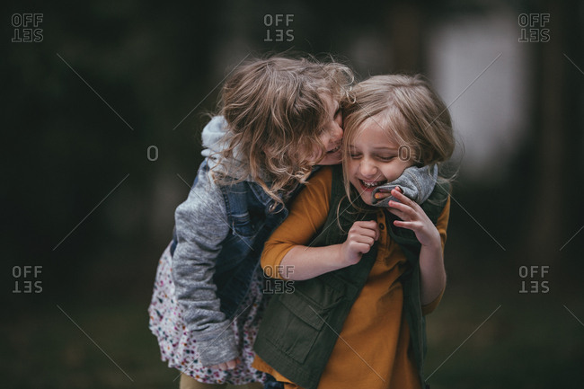 Young girl hugging her sister from behind