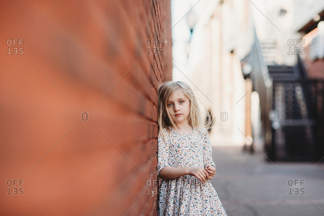 Little girl standing against brick wall in alley