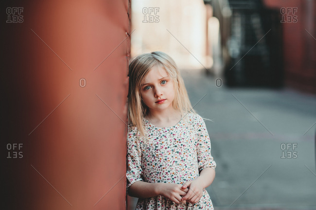 Beautiful young girl in flowered dress leaning against brick wall