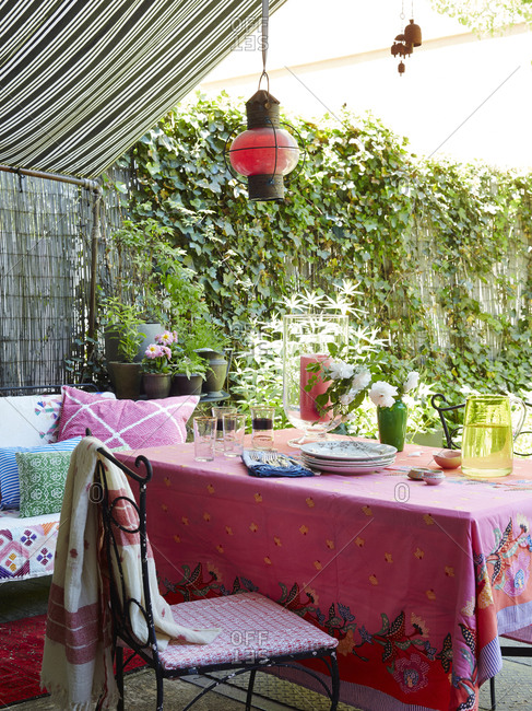 Table set for a meal on a patio with colorful tablecloth