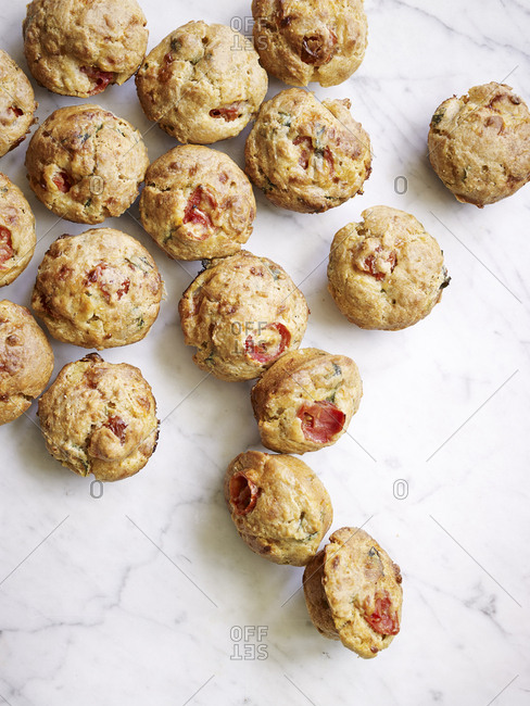Savory basil and tomato muffins on a marble surface