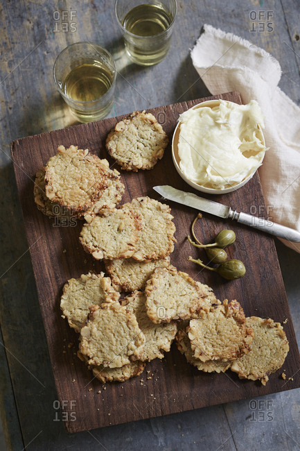 Homemade crackers with cheese spread and olives on a rustic board