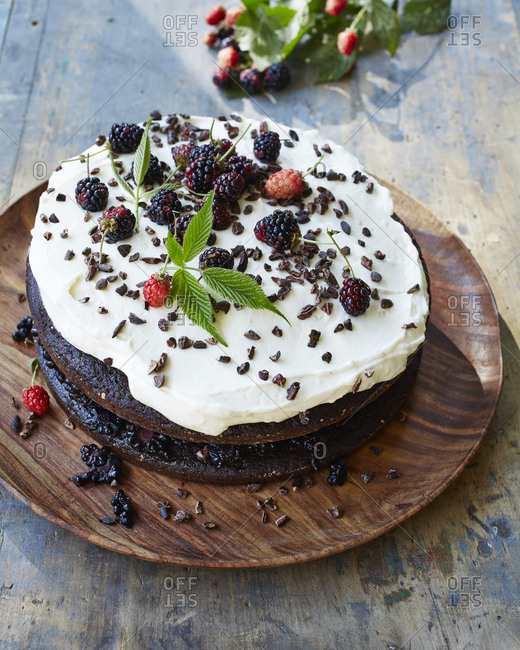 Frosted chocolate blackberry cake garnished with fresh berries