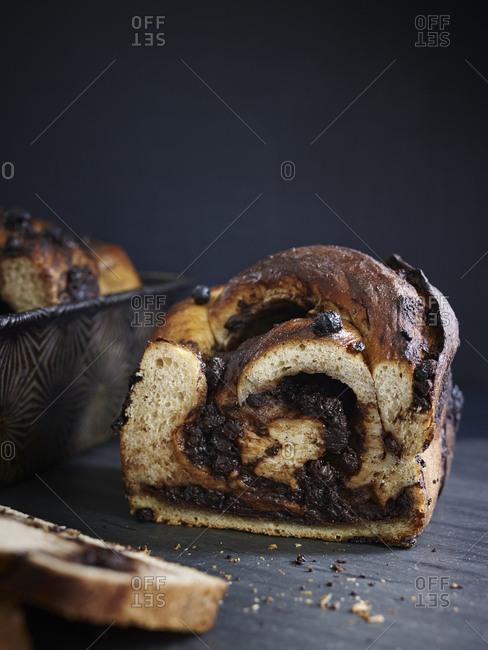 Sliced chocolate babka cake on a wood surface